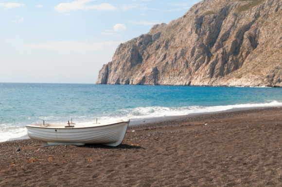View of Kamari Beach in Santorini with a boat sitting on the sand and a tall cliff overlooking the water