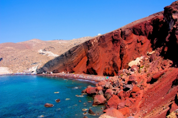 A striking view of the red rocks overlooking the azure water at Santorini's famous Red Beach
