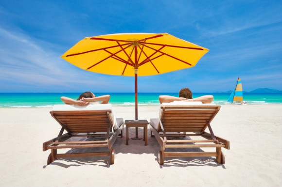 Two people sunbathing on sunloungers on the beach under an umbrella.