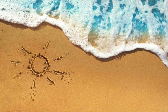 The picture of the sun drawn in the sand as the waves come onto the beach.