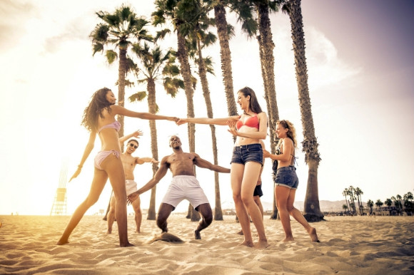 Friends playing a Caribbean game of limbo on the beach on a sunny day.