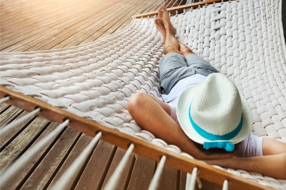 A man having a siesta and relaxing on the beach inside a hammock.