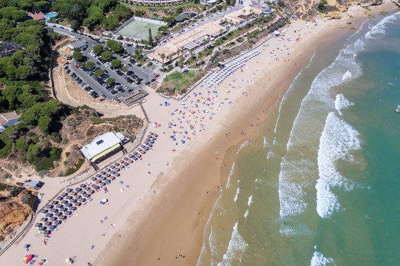 Aerial view of Olhos de Agua Beach, Albufeira in Portugal's Algarve with golden sand and emerald waters lapping the shore