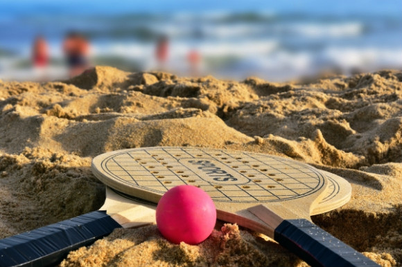Two bats and a pink ball laid on the beach.