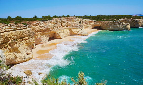A beautiful sunny beach in the Algarve surrounding by limestone cliffs and the Atlantic Ocean