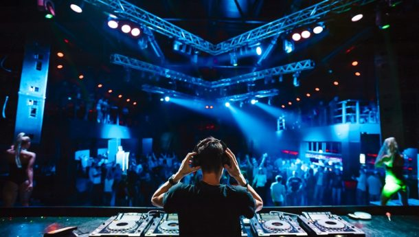 DJ playing music in a club while party-goers dance the night away
