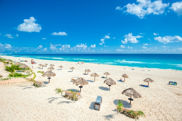 Cancun Beach in Mexico with straw umbrellas and tropical waters
