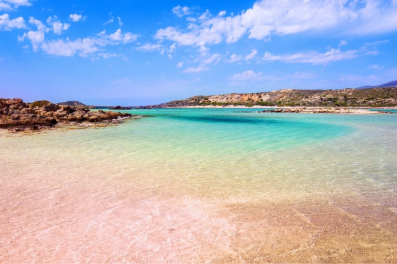 The pink grains of Elafonissi Beach in Crete and the turquoise-tinted sea and surrounding mountain landscape of Greece.