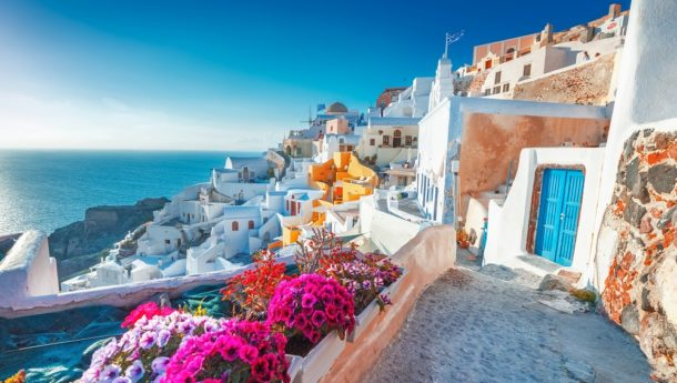 Mesmerising views of Fira and its whitewashed blue-domed houses and floral landscapes in Santorini, Greece.