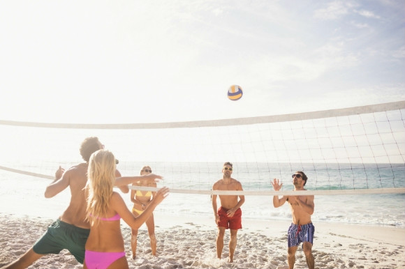 A group of people playing volleyball on the beach.