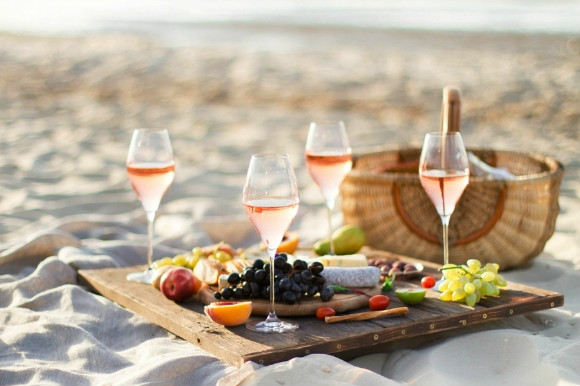 Beach picnic serving fruit, cheese and wine from a wooden basket.