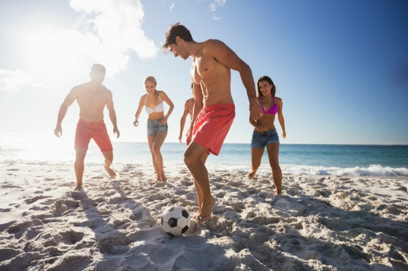 Friends playing football on the beach on a sunny day.