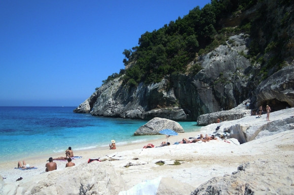 The beautiful white sand beach of Cala Goloritze in Sardinia Italy. Holidaymakers are sunbathing on the soft grains on a sunny day!