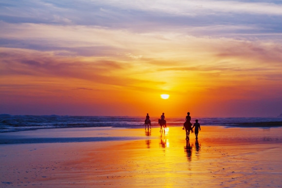 A family horse riding along the beach under the sunset.