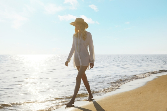 Woman walking along the sand as part of Ikos resort's beach lifestyle concept