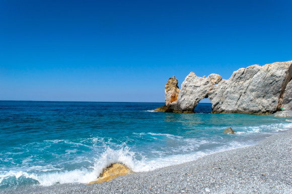 The pebbly Lalaria Beach in Skiathos with cliffs sitting in the water and waves lapping the shore