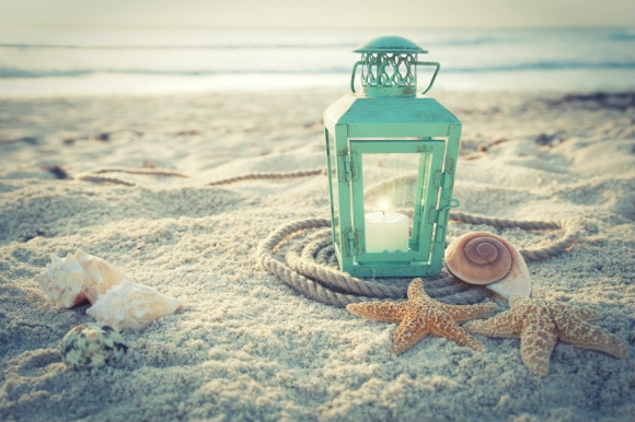 Lantern, shells and star fish nestled in the soft grains of sand on the beach.