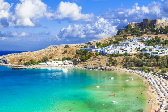 Panoramic view of Lindos shimmering blue bay, village and Acropolis in Rhodes Greece.