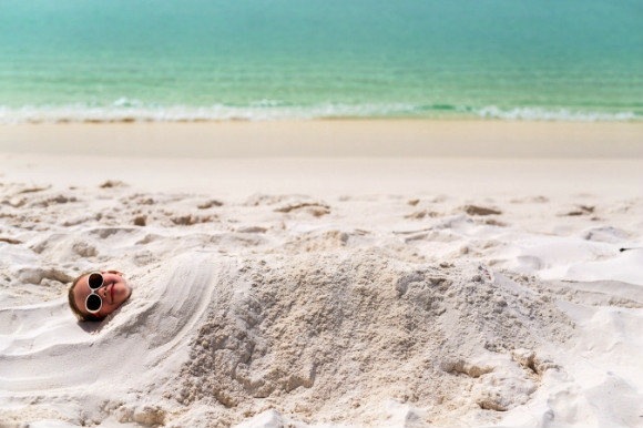 Little girl with sunglasses buried under the sand on the beach.