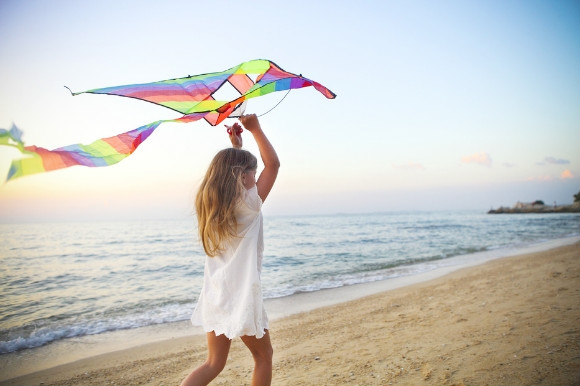 Little girl running and trying to fly a kite on the beach