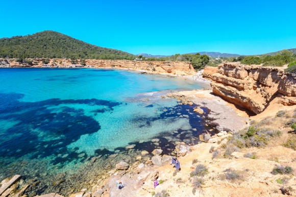 Sapphire waters and pebbly coast of Sa Caleta beach in Ibiza