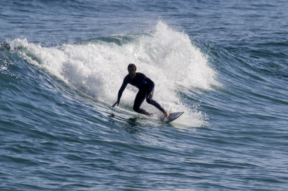 Man surfing in the Atlantic Ocean on Tavira Island Beach in Portugal's Algarve