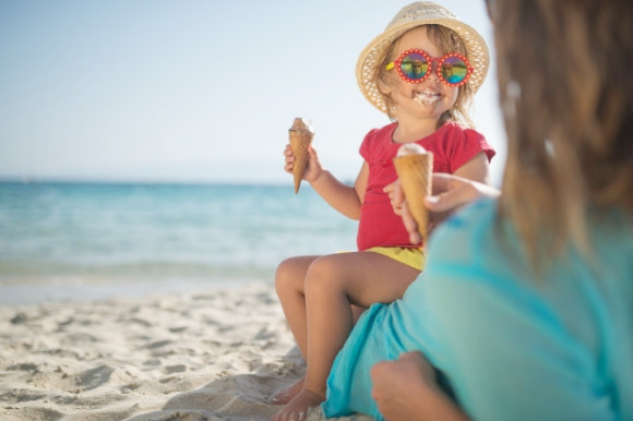 Little girl eating a messy ice cream on the beach with her mum