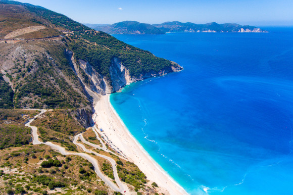 The breathtaking views from the top of Myrtos Beach in Kefalonia backed by lush green cliffs