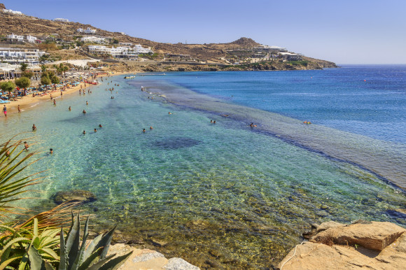 The popular Paradise Beach in Mykonos filled with tourists and backed by traditional whitewashed houses