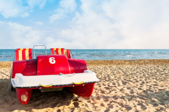 Red peddle boat on the beach with the sea in the background.