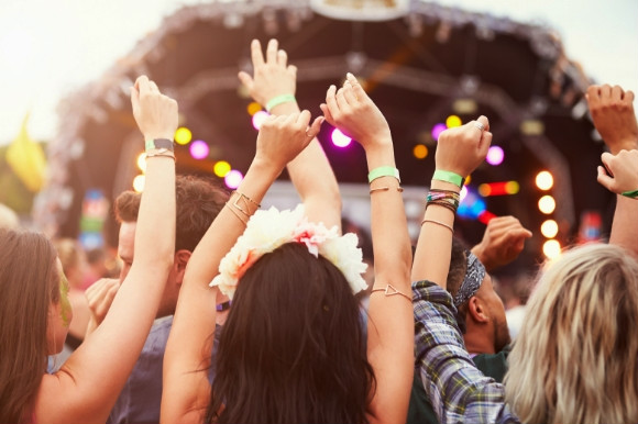People dancing with their hands in the air in front of the stage at a festival in Spain.