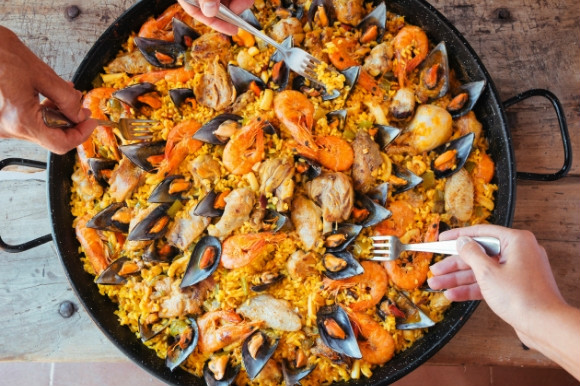 Forks tucking into a tasty bowl of seafood Paella in Spain.