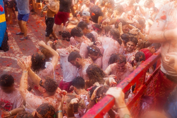 Tomatoes being shot at people during the wild La Tomatina Festival in Spain.