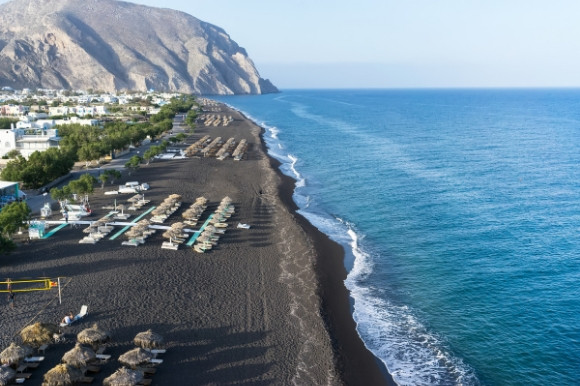 The volcanic black sands of Perissa Beach in Santorini lined with sunloungers and backed by whitewashed houses