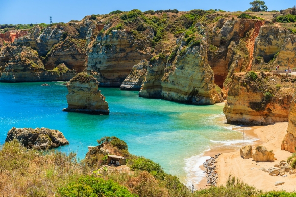 Portugal's famous Praia Dona Ana Beach with stunning views of the surrounding cliffs and clear blue water