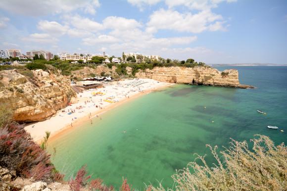 The emerald waters and limestone cliffs of Praia da Senhora da Rocha in Portugal's Algarve