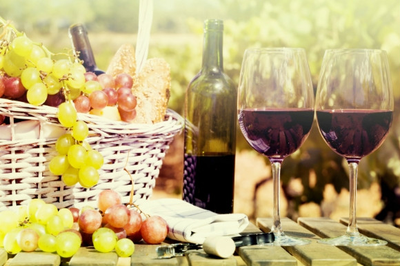 Ripe grapes in a picnic basket and red wine served in a glass from the bottle on a sunny day in Spain.