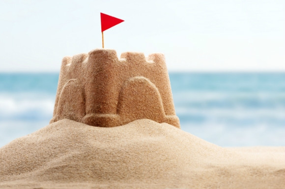 A sandcastle with a red flag perched on a spot of sand on the beach.