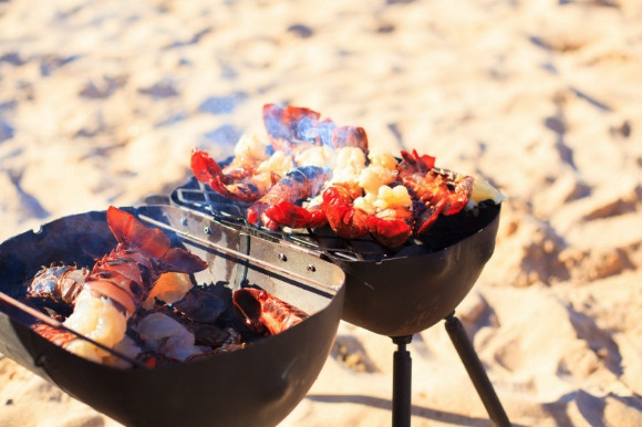 Grilled meats and fish on a smokey barbecue on the beach.