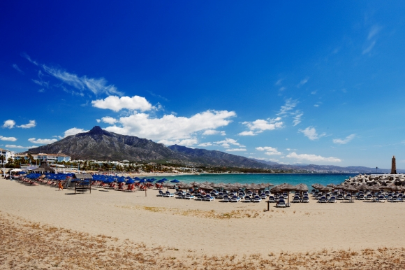 View of the popular Puerto Banus Beach in Marbella scattered with sunloungers.