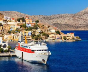 Overlooking the Harbour at Symi Greece with a ferry in Port. Greece Europe.