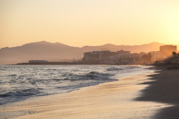 A sunset view of Bounty Beach in Marbella backed by surrounding buildings