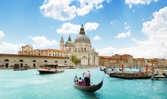 The beautiful Grand Canal in Venice surrounded by Basilica Santa Maria della Salute with a travelling gondola