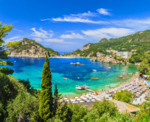 The breathtaking Palaiokastritsa Beach on the island of Corfu, surrounded by vast greenery and lined with sunloungers