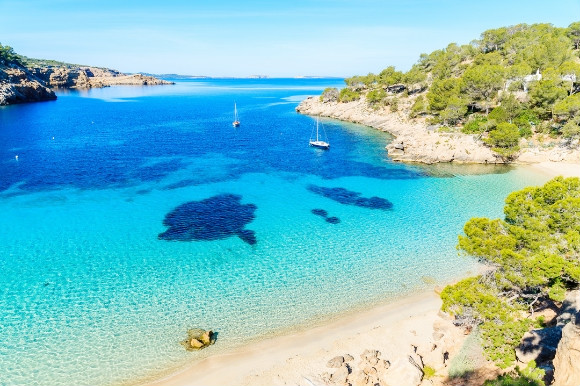 Caribbean-like waters dotted with fishing boats in Cala Salada Ibiza