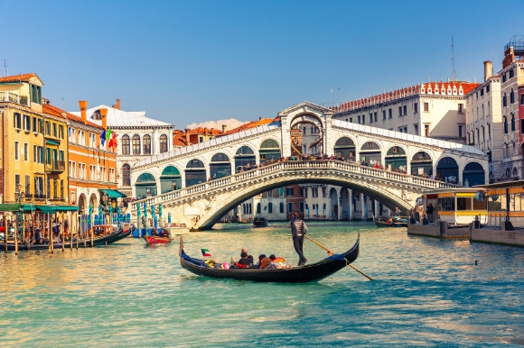 The famous Rialto Bridge in Venice surrounded by buildings with a gondola gliding along the water