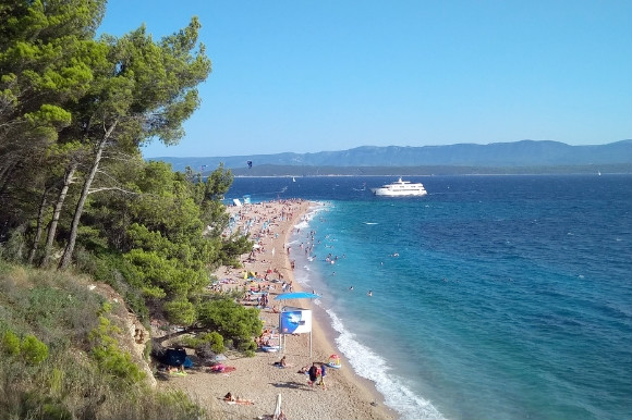 Lush green landscapes leaning over the golden stretches of Zlatni Rat Beach in Croatia.