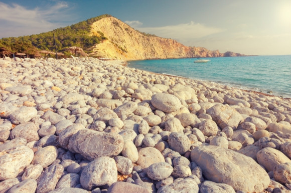 Mixing pebbled shores with soft grains of sand, Cala Jondal beach is breathtaking in Ibiza