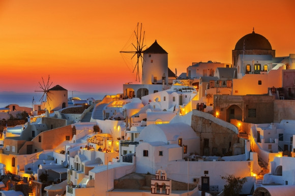 The golden backdrop of the sun setting over the whitewashed resort of Oia in Santorini, Greece.
