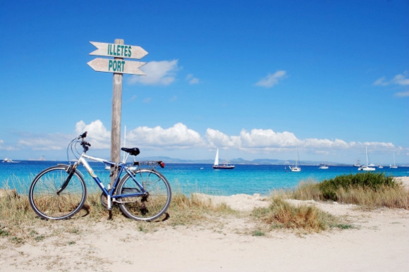 Toe-sinking powder white sands of Ses Illetes in Formentera the Balearic Islands and signs to the beach with a bike leaning against them